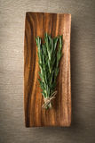 Sprigs of rosemary. On a wooden plate Royalty Free Stock Photos