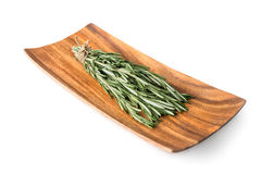 Sprigs of rosemary on a wooden plate. Isolated on white background Stock Photography