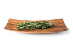 Sprigs of rosemary on a wooden plate. Isolated on white background Stock Image
