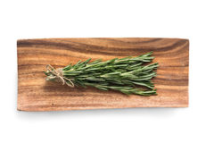 Sprigs of rosemary on a wooden plate. Isolated on white background Stock Images