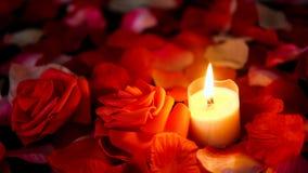 Sprikles nam bloemblaadjes, bloem en kaars het branden lengte toe De dag van decoratievalentine stock footage
