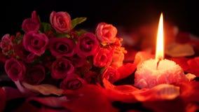 Sprikles nam bloemblaadjes, boeket en kaars het branden lengte toe De dag van decoratievalentine stock video