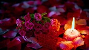 Sprikles nam bloemblaadjes, boeket en kaars het branden lengte toe De dag van decoratievalentine stock footage