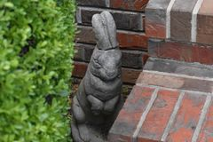 Cement Bunny. Spring is in the air!! Here comes Peter Cottontail waiting by the steps until it is time to hop down the bunny trail stock photo
