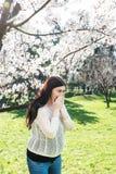 Spring allergy, pollen. A pregnant woman sneezing because of pollen allergy in a garden in the spring Stock Photography