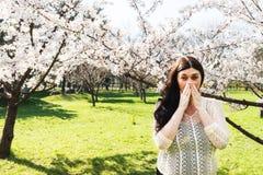 Spring allergy, pollen. A pregnant woman sneezing because of pollen allergy in a garden in the spring Stock Image