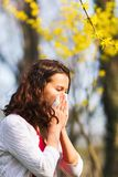 Spring allergy to flowers. Woman blowing her nose in a spring day Royalty Free Stock Image