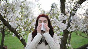 Spring allergy- video with sound. A woman sneezing because of pollen allergy in a garden, spring- front view stock footage