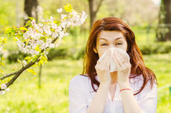 Spring allergy. A woman sneezing because of pollen allergy in a garden in the spring