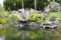 Spring American Northwest home water pond with landscape garden. Spring American Northwest home water pond, large rock with landscape garden Royalty Free Stock Photo