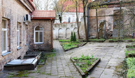 Spring April court yard of the old destroyed  European church. Panoramic urban landscape collage from several outdoor photos Royalty Free Stock Images