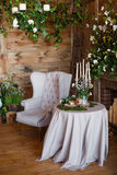 Spring arbor, overgrown with greenery. A cozy corner with a soft arm-chair, a table, candles. Rustic style. Wooden interior with greenery stock photography