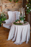 Spring arbor, overgrown with greenery. A cozy corner with a soft arm-chair, a table, candles. Rustic style. Wooden interior with greenery royalty free stock photography