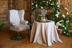 Spring arbor, overgrown with greenery. A cozy corner with a soft arm-chair, a table, candles. Rustic style. Wooden interior with greenery Stock Photos