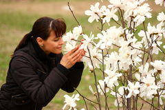 Spring aroma. A woman smelling blossom of a spring bush outside in a park Stock Photo