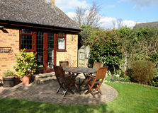Spring arriving in an English back garden. Springtime scene in an English Country Garden with patio table and chairs Royalty Free Stock Images