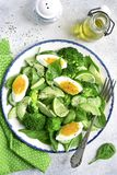 Spring avocado salad with green vegetables and boiled egg.Top vi. Spring avocado salad with green vegetables and boiled egg on a vintage plate over light slate Stock Image