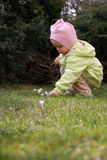 Spring baby. Little baby picking crocuses Royalty Free Stock Photo