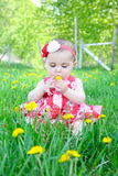 Spring baby. Beautiful brunette baby girl sitting in a field Stock Photo