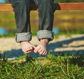 Spring baby park park bench bare feet grass. Hi spring, the child is sitting on a bench in the park feet barefoot above the grass Royalty Free Stock Photography