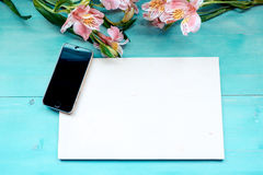 Spring background a blue wooden background with flowers blackboard and mobile phone Royalty Free Stock Photography