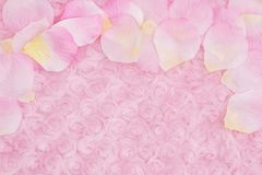 Spring background with a flower petals on pale pink rose plush fabric. With muted mix of shades to provide copy-space for your message stock image