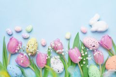 Spring background with flowers, bunny, colorful eggs and feathers on blue table top view. Happy Easter card. Stock Image