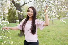 Spring background girl enjoying smell in a flowering garden . copy space . happy young woman stock image