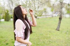 Spring background happy young woman enjoying smell in a flowering garden . copy space royalty free stock photography