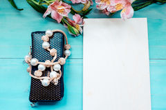 Spring background layout on a blue wooden background with flowers blackboard purse and beads decoration Stock Photo
