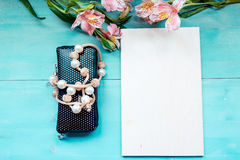 Spring background layout on a blue wooden background with flowers blackboard purse and beads decoration Stock Images
