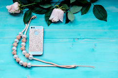 Spring background layout on a blue wooden background with flowers rose and  telephone and beads accessories Stock Photo
