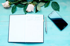 Spring background layout on a blue wooden background with flowers of roses the diary sheets to record pen and phone Royalty Free Stock Photography