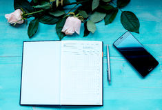 Spring background layout on a blue wooden background with flowers of roses the diary sheets to record pen and phone Stock Photography