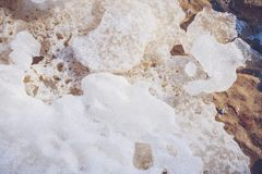 Spring background. Melting ice on beach on a sunny spring day. Stock Photos