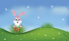 Spring background with pink bunny and Easter eggs. Spring background with a pink cute bunny and red Easter eggs in a green field. Dragonflies on the blue sky Royalty Free Stock Image