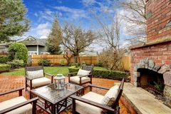 Spring backyard with outdoor fireplace and furniture.