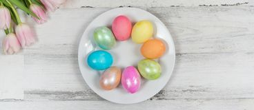Bright beautiful spring banner with fresh tulips and colored Easter eggs. Spring banner with colored eggs and fresh tulips on distressed wood background stock photography