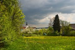 Spring Bavarian village. View of a blooming meadow in front of the Bavarian village Stock Images