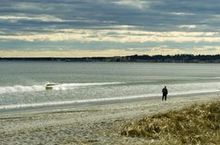 Spring Beaches. A solitary walker on a Maine beach in the late afternoon during late March Royalty Free Stock Images
