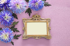 Spring beautiful blue flowers and blank victorian photo frame. Top view image of spring beautiful blue flowers and blank victorian photo frame on wooden stock photography