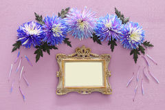Spring beautiful blue flowers and blank victorian photo frame. Top view image of spring beautiful blue flowers and blank victorian photo frame on wooden royalty free stock images