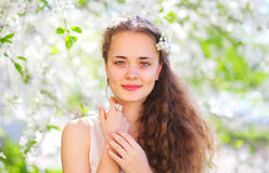 Spring beautiful young girl with curly hair in flowering garden. Spring portrait of beautiful young girl with curly hair in flowering garden royalty free stock photography