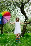 Smiling girl in white dress and rainbow-boots standing in the blooming garden with colorful rainbow-umbrella. Spring beauty concept. Freshness in blooming royalty free stock photography