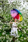 Smiling girl in white dress and rainbow-boots standing in the blooming garden with colorful rainbow-umbrella. Spring beauty concept. Freshness in blooming royalty free stock photo