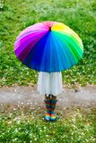 Girl standing in the blooming garden with colorful rainbow-umbrella. Spring, outdoors. Spring beauty concept. Freshness in blooming garden. Girl walking royalty free stock image