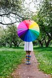 Girl standing in the blooming garden with colorful rainbow-umbrella. Spring, outdoors. Spring beauty concept. Freshness in blooming garden. Girl walking stock images