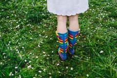 Girl`s legs in colorful rain boots standing on green grass with white petals. Spring, outdoors. Spring beauty concept. Freshness in blooming garden. Rainbow stock images