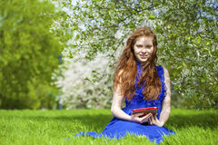 Spring beauty girl with long red blowing hair outdoors Royalty Free Stock Photos