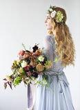 Spring beauty portrait of a bride with a wreath and a bouquet in Stock Photos